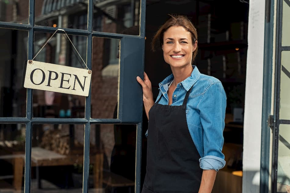 woman standing by her restaurant door